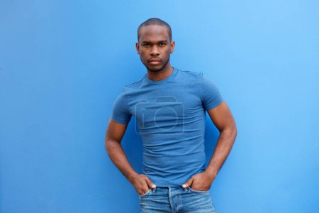 Photo for Portrait of cool young african american guy with t shirt posing against blue background - Royalty Free Image