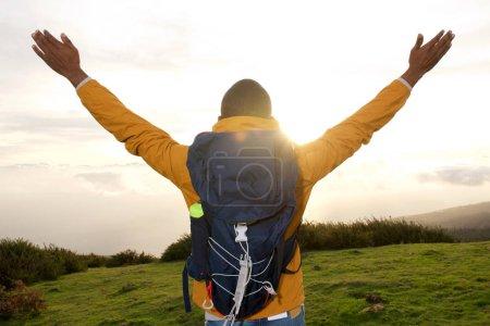 Photo pour Portrait de dos de randonneur avec les bras écartés pendant le coucher du soleil - image libre de droit