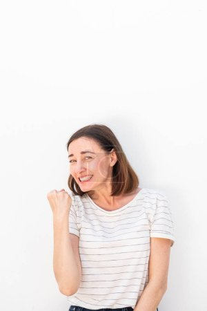 Photo pour Portrait de joyeuse femme d'âge moyen acclamant avec la première pompe par fond blanc - image libre de droit