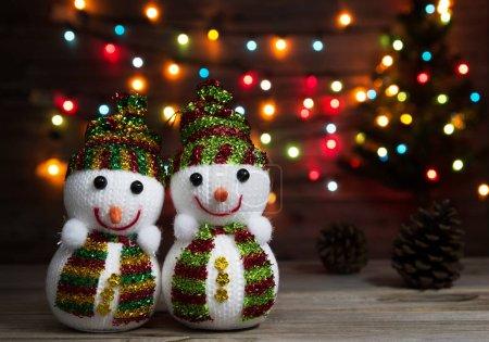 Photo pour Couple de poupées bonhomme de neige sur le déconcentré de la lumière de Noël et le fond de l'arbre de Noël - image libre de droit