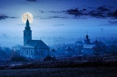 catholic and orthodox churches at foggy night in full moon light. lovely countryside scenery in autumn.