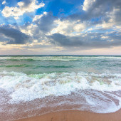 golden beach and green sea on a cloudy evening. beautiful view of waves rolling the coast beneath a glowing sky