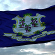 Flag of Connecticut waving in the wind against dee...