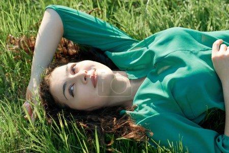 Photo pour Belle fille allongée sur l'herbe le jour ensoleillé, face gros plan, forêt d'été, paysage lumineux avec des ombres - image libre de droit