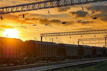Photo pour Infrastructure ferroviaire pendant le beau coucher de soleil et le ciel coloré, wagon pour la cargaison sèche, transport et concept industriel - image libre de droit