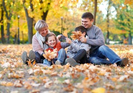 Photo pour Joyeux famille assis dans le parc de la ville d'automne sur les feuilles tombées. Enfants et parents posant, souriant, jouant et s'amusant. Arbres jaune vif . - image libre de droit