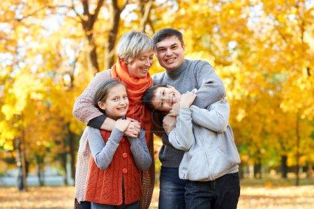 Foto de Feliz familia paseos en otoño Parque de la ciudad. Los niños y los padres posando, sonriendo, jugando y divirtiéndose. Árboles de amarillo brillantes. - Imagen libre de derechos