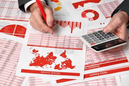 Foto de Contador de negocios usando la calculadora para el cálculo financiero en la oficina. Concepto de contabilidad financiera negocio rojo informes y gráficos. Empleado de la oficina examina informes y horarios. - Imagen libre de derechos