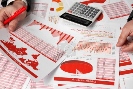 Photo for Businessman accountant using calculator for calculating crypto currency report on desk office. Business financial accounting concept Red reports and graphs. - Royalty Free Image