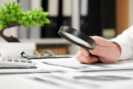Photo pour Homme d'affaires au bureau et en calculant les finances. À l'aide de loupe. Concept comptabilité financière d'entreprise. - image libre de droit
