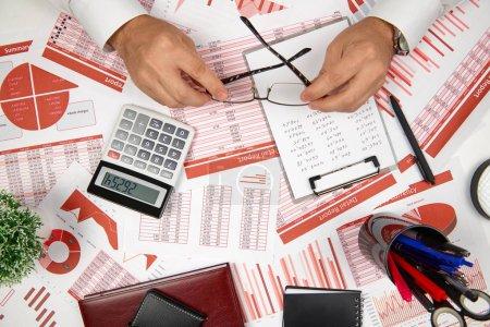 Photo pour Directement au-dessus de la vue de l'homme d'affaires travaillant et calculant la finance, lit et écrit des rapports. Concept de comptabilité financière des entreprises . - image libre de droit
