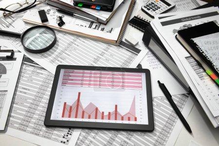 Photo pour Bureau d'affaires gros plan ordinateur tablette avec tableaux et graphiques à l'écran, rapports financiers, analyse et comptabilité, ensemble de documents pour la tenue de livres - image libre de droit