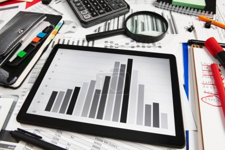 Photo pour Vue de dessus du bureau des employés de bureau - travail avec tablette PC et rapports financiers, analyse et comptabilité, tableaux et graphiques, divers éléments de bureau pour la tenue de livres - image libre de droit