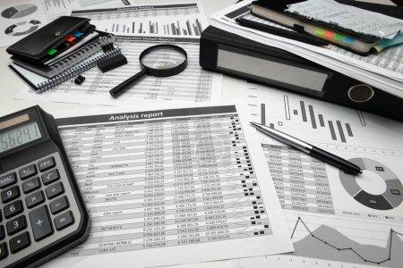 Photo pour Bureau d'affaires gros plan - rapports financiers, analyse et comptabilité, ensemble de documents, tableaux et graphiques, divers éléments pour la comptabilité, calculatrice - image libre de droit