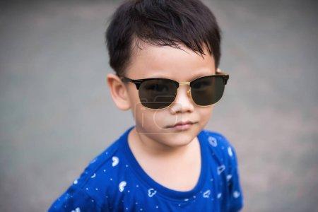 Photo pour Portrait de beau garçon asiatique avec des lunettes de soleil avec un espace de copie pour le texte. Attrayant petit enfant mode . - image libre de droit