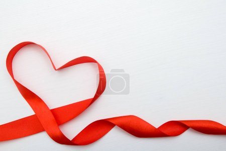 Heart shape made of red ribbon on white wooden Bac...