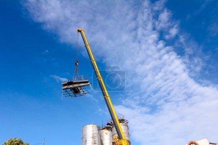 Photo pour Crane fait tomber une partie de la construction de métaux lourds dans un complexe industriel. - image libre de droit