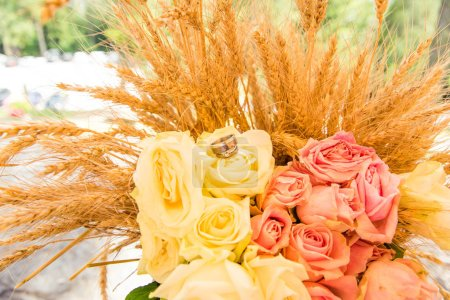 Photo for Wedding Rings on Roses Bouquet and Wheat Ears - Royalty Free Image