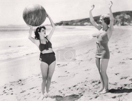 Photo pour Deux femmes jouant au ballon sur la plage - image libre de droit