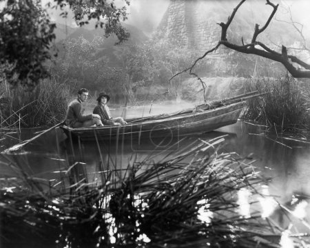 Couple sitting in a rowboat in a marsh