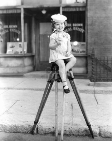 Little sailor girl sitting on a tripod eating an ice cream cone