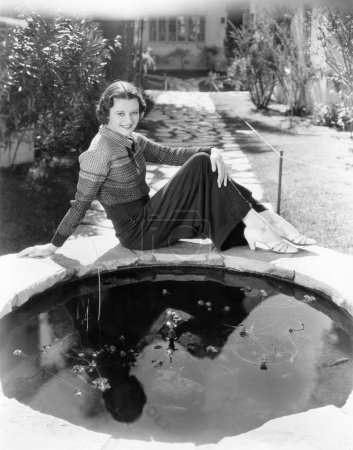 Young woman seated in front of a small reflecting pool