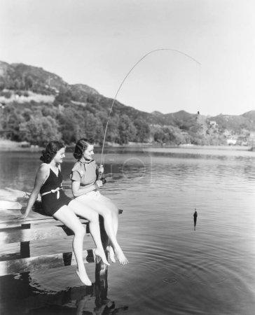 Photo pour Deux femmes pêchant au lac, à l'ancienne - image libre de droit