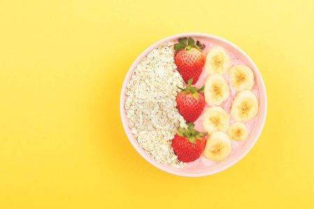 Photo for Strawberry banana smoothie bowl on yellow background. Bright,  colorful and healthy food concept. Flat-lay, top view. Copy space for your text. - Royalty Free Image