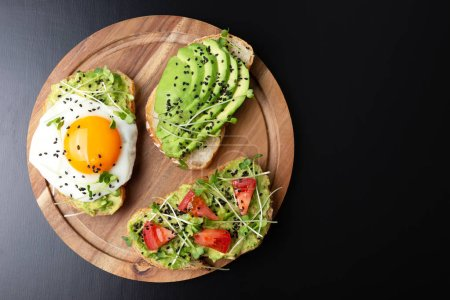 Photo for Three healthy toasts with egg, avocado, micro greens and tomatoes on wooden board. Breakfast or healthy eating concept, plant based food. Flat-lay, top view, copy space. - Royalty Free Image
