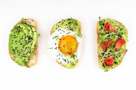 Photo for Three healthy toasts with egg, avocado, micro greens and tomatoes. Breakfast or healthy eating concept, plant based food. Flat-lay, top view. - Royalty Free Image