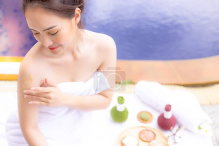 Charming beautiful woman use herbal scrubs for scrubbing skin cells at her arm that make better skin and makes skin rejuvenation. Gorgeous girl wear towel. She feel happy with swimming pool background