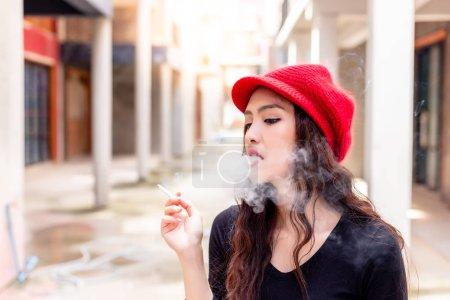 Portrait charmante belle femme est cigarette fumer et soufflant la fumée de sa bouche. Superbe femme fume au public dans la ville. La cigarette est la cause du cancer du poumon et peut tuer