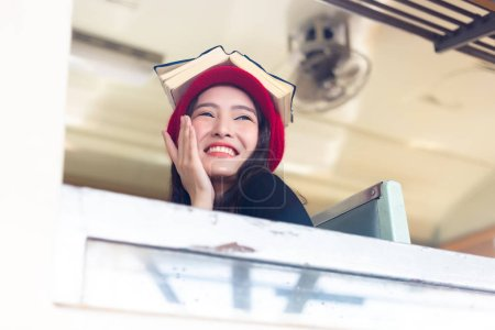 Charming beautiful woman is sitting on a vintage train and put a book on her head. Attractive beautiful girl laughs herself. Gorgeous traveler woman feel relaxed and happy with smiley face. copy space