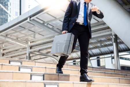 Businessman has important appointment business but a guy cannot go to destination or the place in time. He looks at the watch and worried about his customer will be unsatisfied him. He walk hurrying