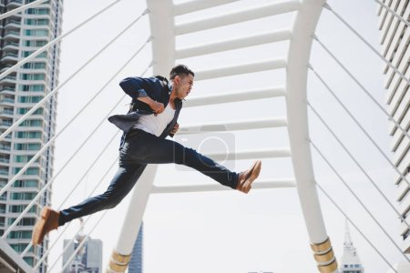 Handsome asian guy is running fast and jumping highly. Attractive young man gets hurry because he gets late and want to go to a place that he gets appointment with city background, copy space.