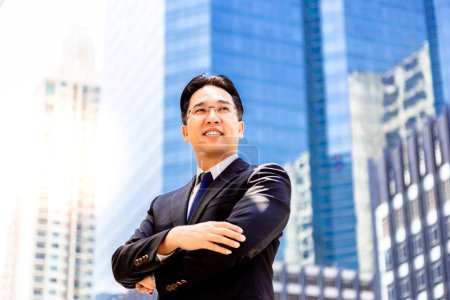 Portrait confidence and determined handsome executive man. Charming handsome businessman is crossing arms and look confident. Handsome guy get successful of business. metropolis background, copy space