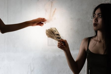 A junkie girl is giving dollars money to a drug dealer for buying heroin, cocaine or narcotic at slums house. The narcotic is so expensive. A drug addict young girl looks thin and illness
