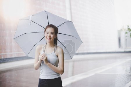Charming beautiful young woman. Attractive beautiful lady hold an umbrella. It is rainy day. Lovely girl is walking at city when light rain. Its rainy season. She look so relaxed and happy. copy space