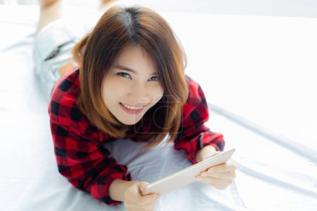Portrait charming beautiful woman. Attractive beautiful woman is playing tablet on bed in the morning. Attractive beautiful girl gets happiness with smiley face. Asian woman feels relaxing. copy space