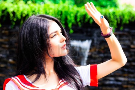 Attractive beautiful woman raise hand for protecting strong sunlight in afternoon that make her sore eyes when look at sky. Gorgeous woman gets afraid sunlight because sunlight is cause of skin cancer