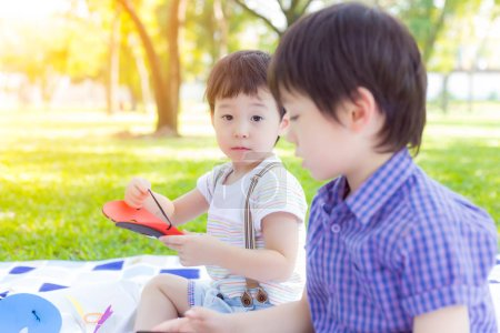 Photo for Handsome little boy looking at camera during he playing toy at park and staying with older brother. Lovely kid is adorable or looks innocent. He is preschool child. He loves playing with his brother - Royalty Free Image