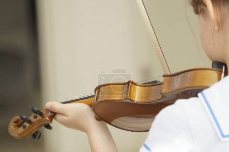 Girl playing violin in white