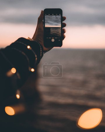 Male hand holding camera and taking shot of sunset on river background