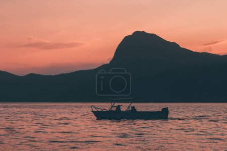 Two men fishing in boat sunset sky sea shore mountains