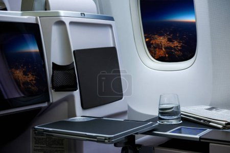 Photo for Glass of water standing on table in aircraft - Royalty Free Image
