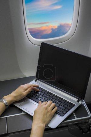 Photo pour Femme d'affaires travaillant avec ordinateur portable sur avion - image libre de droit