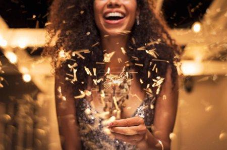 Photo pour Joyeux jeune femme tenant seul scintillant dans la main en plein air. Détail de fille africaine célébrant la veille du Nouvel An avec la lumière du bengale. Gros plan de belle femme tenant un bâton étincelant lors de la soirée de fête . - image libre de droit