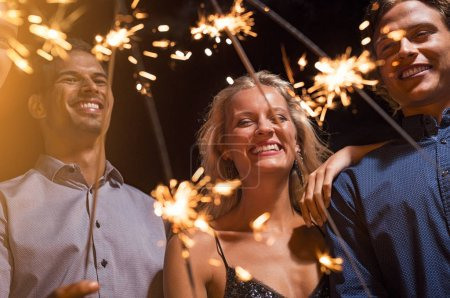 Happy beautiful woman and men celebrating festival with bengal lights. Cheerful multiethnic group of friends enjoying with sparkling sticks. Smiling girl and guys celebrate new year's eve with firework.