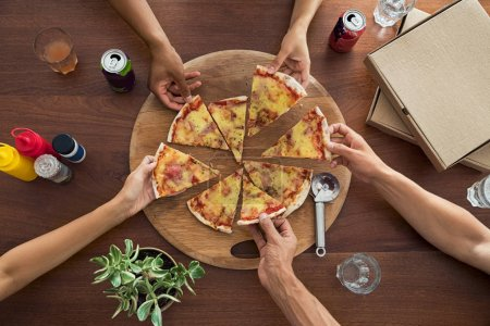 Top view of group of hands sharing italian pizza. High angle view of friends hands at restaurant picking pizza slices from wooden cutting board. Multiethnic people taking a triangle of pizza at home.