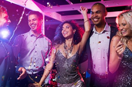 Group of multiethnic happy friends dancing at disco club. Group of young men and beautiful women having fun at celebration with confetti. Smiling guys and elegant girls enjoying night life with colored light.